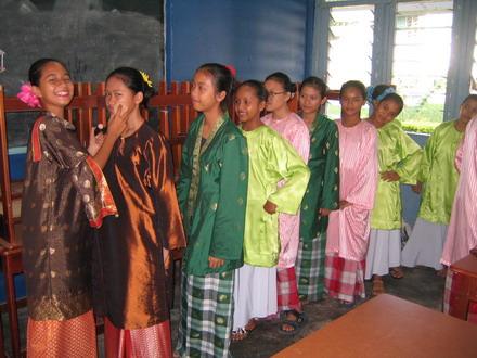 Penari perempuan sedang berbaris untuk di 'touch-up' oleh penari senior.